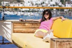 усмехаясь женщина наслаждаясь летними каникулами лежа на sunbed в баре моря Стоковое Изображение