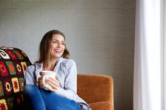 Усмехаясь женщина наслаждаясь чашкой чаю дома Стоковые Фото