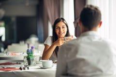 Усмехаясь женщина на дате в ресторане, имеющ переговор над едой в гостинице Положительные эмоции, влюбленность, привязанность Стоковые Фотографии RF