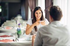 Усмехаясь женщина на дате в ресторане, имеющ переговор над едой в гостинице Положительные эмоции, влюбленность, привязанность Стоковое Изображение