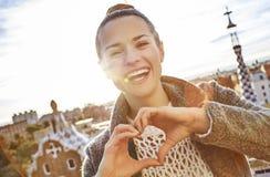 Усмехаясь женщина на Guell паркует показывать руки сформированные сердцем Стоковые Изображения RF