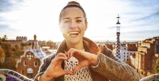 Усмехаясь женщина на Guell паркует показывать руки сформированные сердцем Стоковое фото RF