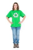 Усмехаясь женщина нося рециркулирующ представлять футболки стоковые фото