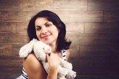 Усмехаясь женщина обнимая кролика Стоковое Изображение RF