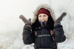 Усмехаясь женщина одела теплое бросающ вверх ее руки в сюрпризе Стоковые Изображения RF