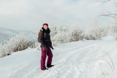 Усмехаясь женщина одела теплое наслаждающся прогулкой в снежной стране Стоковые Изображения RF