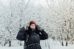Усмехаясь женщина одела теплый идти через лес в зиме Стоковое Изображение