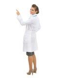 Усмехаясь женщина доктора указывая на космос экземпляра Стоковая Фотография RF