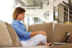 Усмехаясь женщина ослабляя дома с компьтер-книжкой Стоковое Изображение RF