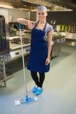 Усмехаясь женщина очищая пол кухни стоковое изображение rf