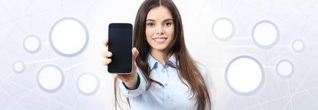 Усмехаясь женщина показывает smartphone, социальные средства массовой информации, социальную сеть стоковая фотография
