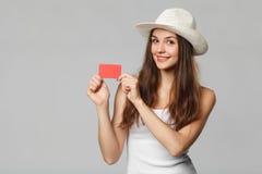 Усмехаясь женщина показывая кредитную карточку кредита без обеспечения в белой футболке, изолированной над серой предпосылкой Стоковое Фото