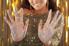 Усмехаясь женщина показывая покрытые ладони в ярком блеске стоковая фотография