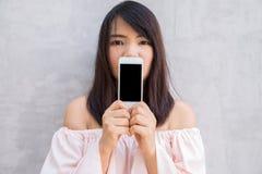 Усмехаясь женщина показывая пустой smartphone экранирует положение на бетонной стене Стоковые Изображения