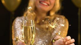 Усмехаясь женщина показывая стекло шампанского и светлого Бенгалии к камере, партии сток-видео