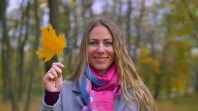 Усмехаясь женщина покрывая ее сторону с желтыми лист сток-видео