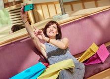 Усмехаясь женщина постаретая серединой принимая Selfie Стоковые Изображения