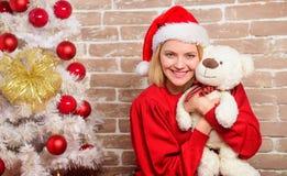 Усмехаясь женщина празднуя рождество Счастливая девушка в шляпе Санта Клауса Подарки рождества поставки Партия Новый Год весело стоковая фотография