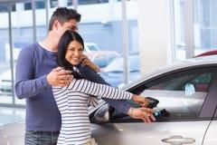 Усмехаясь женщина представляя ее новый автомобиль Стоковые Изображения RF