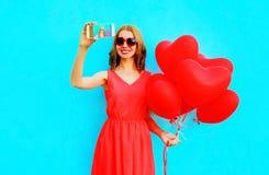усмехаясь женщина принимает автопортрет изображения на владении smartphone стоковые изображения