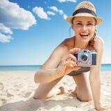 Усмехаясь женщина принимая фото с ретро камерой фото на пляже стоковые изображения rf