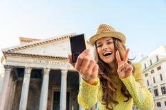 Усмехаясь женщина принимая selfie на пантеон делая жест победы Стоковые Фотографии RF