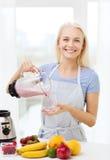 Усмехаясь женщина при blender подготавливая встряхивание дома Стоковые Изображения