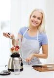 Усмехаясь женщина при blender подготавливая встряхивание дома Стоковое фото RF