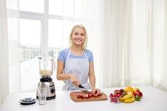 Усмехаясь женщина при blender подготавливая встряхивание дома Стоковое Фото