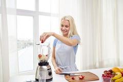 Усмехаясь женщина при blender подготавливая встряхивание дома Стоковая Фотография