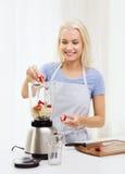 Усмехаясь женщина при blender подготавливая встряхивание дома Стоковая Фотография RF