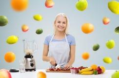 Усмехаясь женщина при blender подготавливая встряхивание плодоовощ Стоковые Изображения