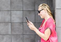 Усмехаясь женщина проверяет мобильный телефон Стоковые Изображения RF
