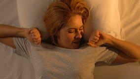Усмехаясь женщина протягивая в кровати, здоровом сне для кожи красоты, добром утре видеоматериал