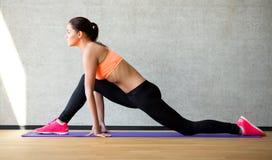 Усмехаясь женщина протягивая ногу на циновке в спортзале Стоковые Фотографии RF