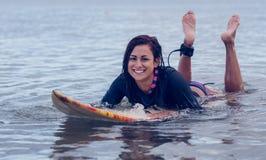 Усмехаясь женщина плавая над surfboard в воде Стоковые Фотографии RF