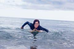 Усмехаясь женщина плавая над surfboard в воде Стоковые Фото
