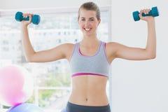 Усмехаясь женщина работая с гантелями в студии фитнеса Стоковое фото RF