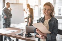 Усмехаясь женщина работая с ее командой Стоковое Изображение