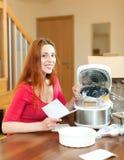 Усмехаясь женщина распаковывая и читая руководство потребителя для нового глинян-po Стоковая Фотография RF