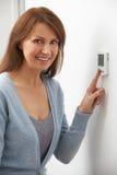 Усмехаясь женщина регулируя термостат на системе отопления домов Стоковое фото RF
