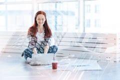 Усмехаясь женщина связывая текст тесьмой на ее компьтер-книжке Стоковые Изображения RF