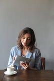Усмехаясь женщина сидя внутри помещения используя планшет Стоковые Фото