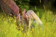 Усмехаясь женщина сидя в луге с ее аравийской лошадью Стоковые Фотографии RF