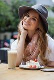 Усмехаясь женщина сидя едой на таблице в магазине кафа Стоковые Изображения RF
