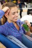 Усмехаясь женщина сидя и держа стекло чая свежей мяты стоковые фотографии rf