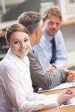 Усмехаясь женщина сидя на деловой встрече с коллегами Стоковая Фотография