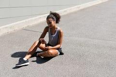 Усмехаясь женщина сидя на дороге Стоковые Изображения