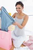 Усмехаясь женщина сидя на поле с новыми платьем и хозяйственной сумкой Стоковое Изображение