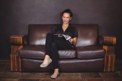 Усмехаясь женщина сидя на софе и читать кассету Стоковые Фотографии RF